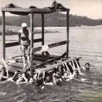 Pinewood swim raft at Sly Park, summer of 1962. Larry Slater on the far left, Ron Parker on the far right, Margaret Slater on the raft. Students unidentified.